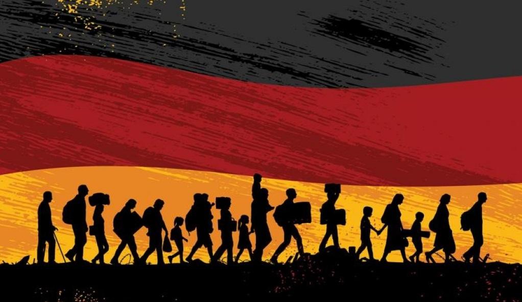 رتل من المهاجرين يسيرون أمام العلم الألماني نحو الاندماج الحقيقي